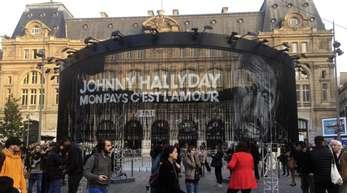 Passanten hören das posthum veröffentlichte Album «Mon pays c'est l'amour«» in paris.