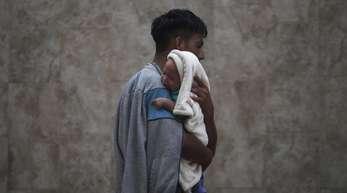 Ein Migrant hält seinen kleinen Sohn im Arm. Die Menschen aus Mittelamerika sind auf der Flucht vor Gewalt und bitterer Armut.