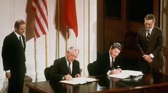 US-Präsident Ronald Reagan (r) und der sowjetische Parteichef Michail Gorbatschow unterzeichnen am 08.12.87 in Washington den INF-Vertrag.
