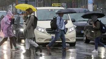 Bei Sprühregen und Temperaturen um zehn Grad überqueren Fußgänger eine Straße am Potsdamer Platz in Berlin.