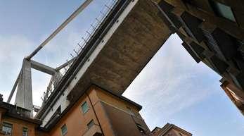 Ein Teil der eingestürzten Morandi-Brücke hängt bedrohlich über evakuierten Wohnhäusern.