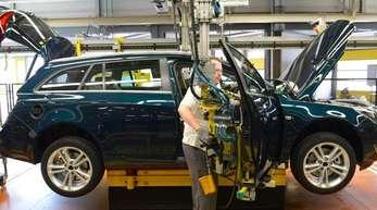 Ein Opel-Mitarbeiter montiert im Opel-Stammwerk eine Tür an einem Opel Insignia.