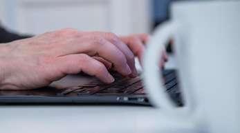 """Der Kaffeebecher neben der Tastatur statt auf dem Tisch des Cafes """"nebenan"""" - viele Beschäftigt arbeiten ohne Pause."""