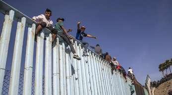 Migranten aus Mittelamerika sitzen in Tijuana auf dem Grenzzaun zwischen Mexiko und den USA.