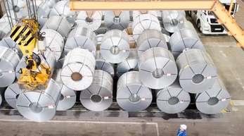 Ein Mitarbeiter transportiert mit einem Kran auf dem Gelände der Salzgitter AG Coils (aufgewickelte Metallbänder).