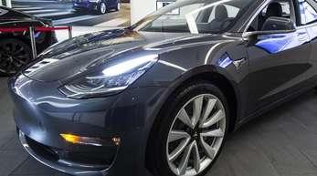 Das Elektroauto Model 3 von Tesla steht in einem Ausstellungsraum.