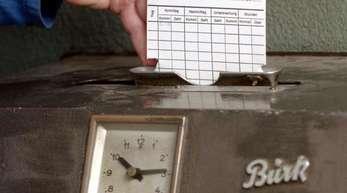 In einem Krefelder Unternehmen wird eine Karte in ein Arbeitszeiterfassungsgerät, eine so genannte Stechuhr, gesteckt.
