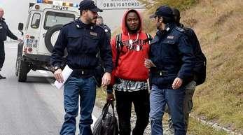 Italienische Polizisten überprüfen einen Mann nahe der Grenze zu Frankreich.