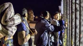 Migranten mit Matratzen und Rucksäcken am Zaun der Grenze zwischen USAund Mexiko.
