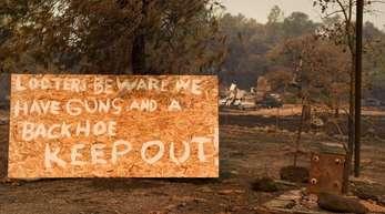 Der Ort Paradise nördlich von Sacramento gleicht nach dem «Camp»-Inferno einer Geisterstadt. An der Zugangsstraße warnen Grundstücksbesitzer Plünderer vor Diebstählen.