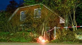 Eine Grableuchte steht neben einer Polizeiabsperrung am Eingang zu einem Haus in Wittenburg. Hier ist ein 85 Jahre alter Mann mit einem Messer getötet worden.