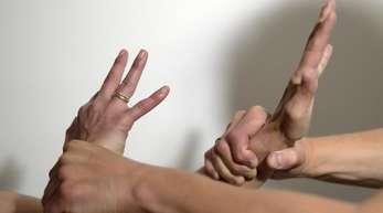 Die Arme eines Mannes (r) halten mit Gewalt die Arme einer Frau fest.