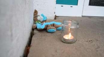 Ein Teddy liegt neben einem Teelicht im Eingangsbereich eines Wohnhauses im Stadtteil Winzerla.