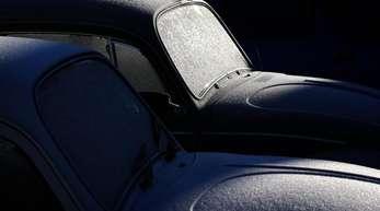 Zwei mit Eiskristallen überzogene VW-Käfer glitzern im Sonnenschein.