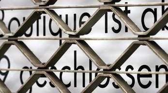 Mit einem Rollgitter ist eine geschlossene Boutique abgesperrt. Seit Jahren sinkt dank guter Konjunktur die Zahl der Firmenpleiten in Deutschland.