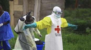 Helfer reinigen sich nach der Arbeit in einem Behandlungszentrum gegen Ebola mit Desinfektionsmittel.