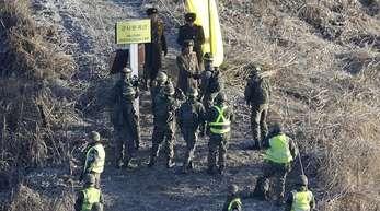 Ein Soldat der südkoreanischen Armee (M, unten) gibt einem Soldaten aus Nordkorea (M, oben) an der Demarkationslinie die Hand.