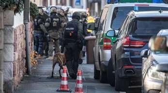 Polizisten stehen am Rand eines Gebäudes, in dem sich ein bewaffneter Mann verschanzt hat.