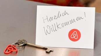 Ein Schlüssel mit einem Airbnb-Anhäger und eine Herzlich-Willkommen-Karte in der Wohnung eines Airbnb-Gastgebers.