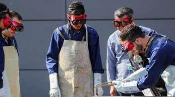 Flüchtlinge in Bayern lernen über den Wiederaufbau von Häusern und üben die Arbeit mit einem Schweißbrenner.