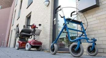 Ein Rollator und ein Elektromobil stehen vor einer Seniorenwohnung.