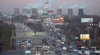 Kein Zustand auf Dauer:Verkehrsstau auf einer großen Straße in Moskau, im Hintergrund qualmen große Kraftwerke.