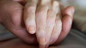 Ein Altenpfleger hält die Hand einer pflegebedürftigen Frau.
