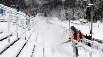 Helfer befreien die Zuschauertribünen in Ruhpolding vom Schnee.