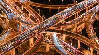 Das Bild zeigt den Blick auf ein Autobahnkreuz in Shanhgai bei Nacht.