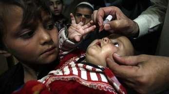 Ein pakistanischer Helfer impft ein Kind mit Tropfen.