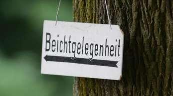 Ein Schild mit der Aufschrift «Beichtgelegenheit» hängt an einem Baum.