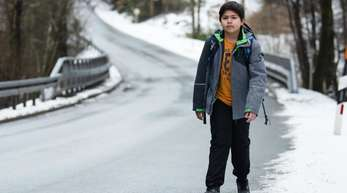 Marc läuft eine kurvige Landstraße entlang. Der Junge muss rund zwei Kilometer zu Fuß zur Haltestelle seines Schulbusses laufen.