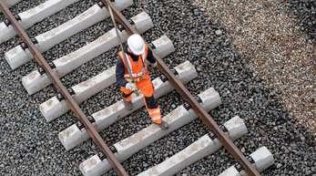 Ein Arbeiter geht über eine noch nicht fertige Gleisanlage der Bahn.