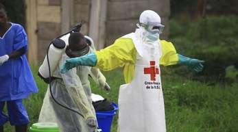 Ein Helfer des Roten Kreuzes wird nach einem Einsatz in einem Ebola-Behandlungszentrum von einem Kollegen mit Desinfektionsmittel eingesprüht.