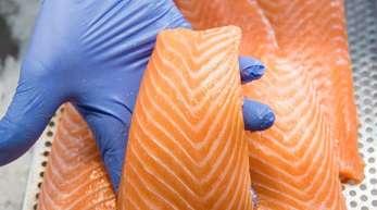 Ein Mitarbeiter präsentiert in einem Fischmarkt in einer Kühlvitrine liegenden Lachs.