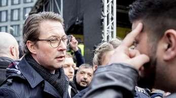 Andreas Scheuer (CSU), Bundesverkehrsminister, unterhält sich bei einer Kundgebung von Taxifahrern am Bundesverkehrsministerium mit einem Teilnehmer.