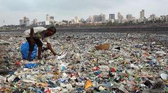 Ein Mann sammelt Plastik und andere wiederverwertbare Materialen an der von Plastiktüten und sonstigen Müll übersäten Küste vor Mumbai.