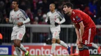 Münchens Javi Martinez zeigt sich geknickt während im Hintergrund Spieler des FC Liverpool ein Tor feiern.
