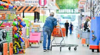 Ein Kunde schiebt in Darmstadt seinen Einkaufswagen durch einen Baumarkt. Wie so viele Branchen haben auch die Baumärkte einen mächtigen Konkurrenten: das Internet.