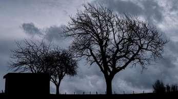 Dunkle Regenwolken sind über einem Feld bei Hattendorf in Niedersachsen zu sehen.