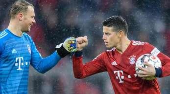 Dreifachtorschütze James Rodríguez (r) feiert mit Torwart Manuel Neuer den Sieg des FC Bayern München.