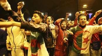 Menschen feiern in Algier nach der Bekanntgabe des Rücktritts.