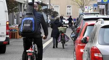 In Karlsruhe fahren Fahrradfahrer an Autos vorbei, die auf einem Parkstreifen stehen.