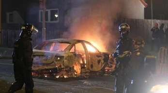 Polizisten vor einem brennenden Auto.