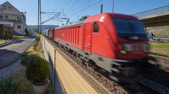 Ein Güterzug fährt im Rheintal an einer direkt am Gleisbett platzierten niedrigen-Lärmschutzwand vorbei.