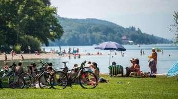 Badegäste liegen am Starnberger See an einem Strand. Der Landkreis ist der reichste in Deutschland.