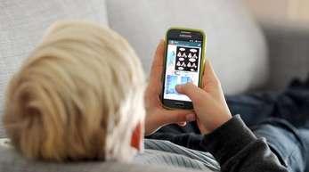Keine Bücher, dafür täglich Hunderte von Kurznachrichten: ein Jugendlicher blickt auf sein Smartphone.