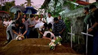 Verwandte platzieren Blumen nach der Beerdigung von Opfern, die bei der Bombenexplosion am Ostersonntag starben.