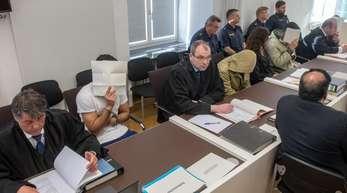 Die vier Angeklagte sitzen neben ihren Anwälten im Verhandlungssaal des Amberger Amtsgerichts.