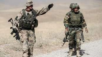 Ein Bundeswehrsoldat und kurdische Peshmerga im irakischen Erbil.